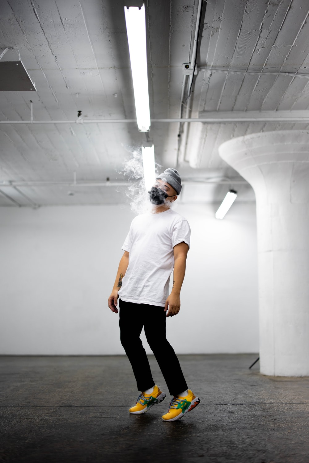 man in white crew neck t-shirt and black pants standing on gray floor