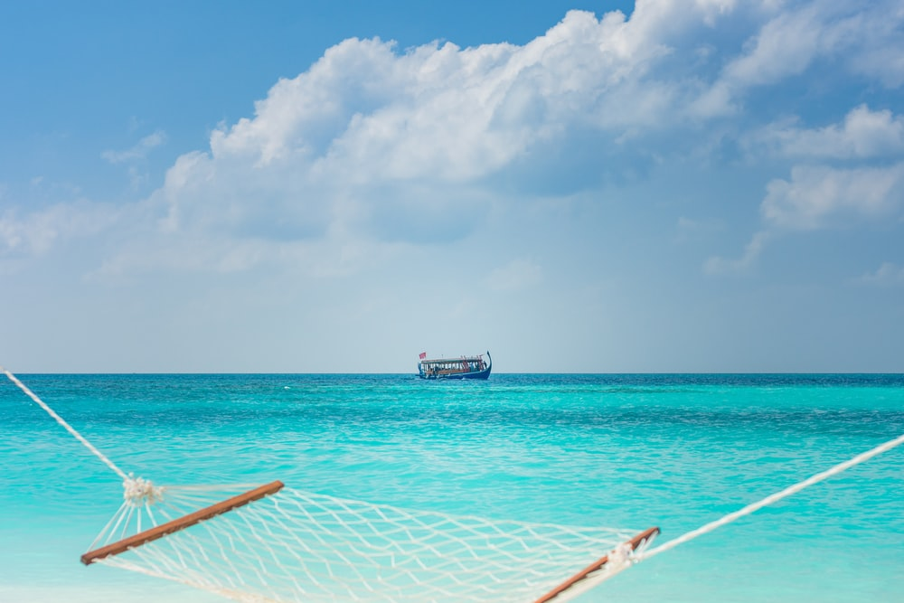 white and blue boat on sea under blue sky during daytime
