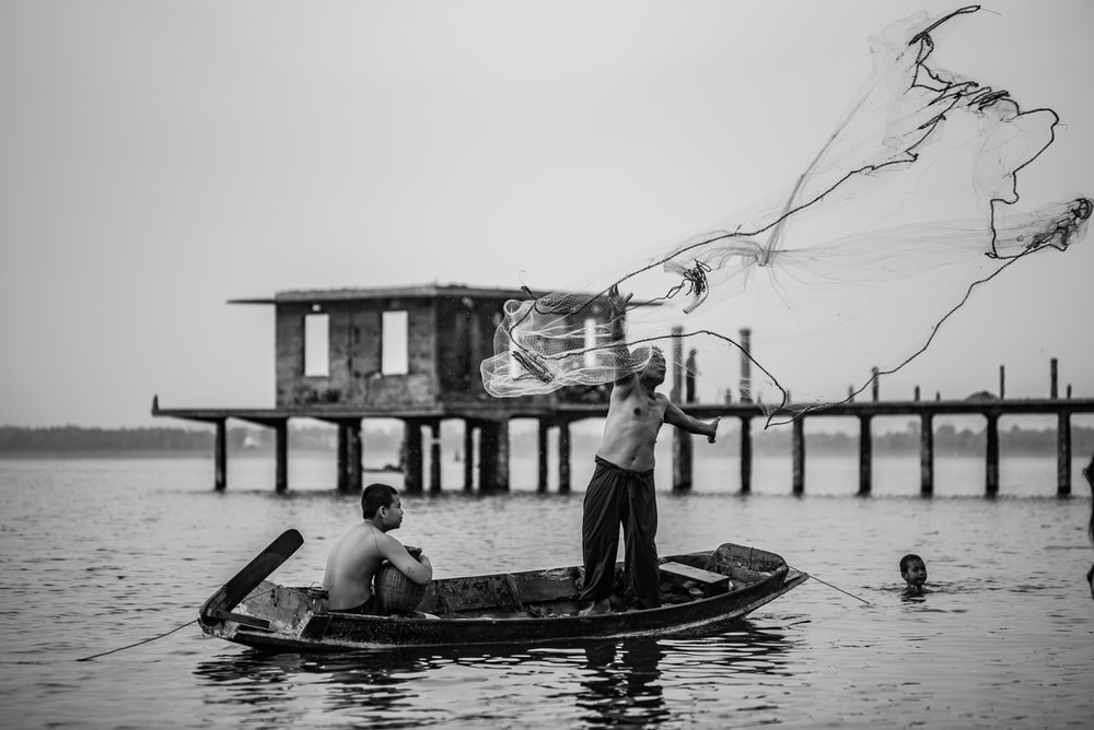 grayscale photo of man in boat