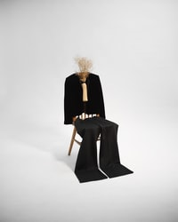 woman in black coat sitting on brown wooden chair