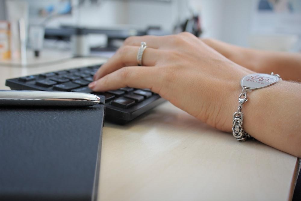 person wearing silver ring using black computer keyboard