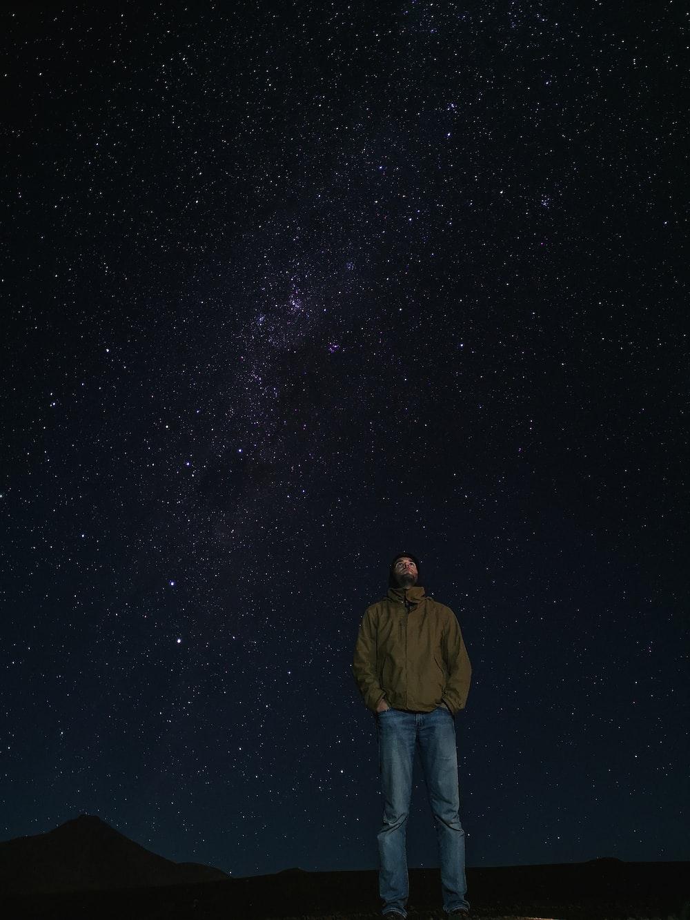man in brown jacket standing under starry night