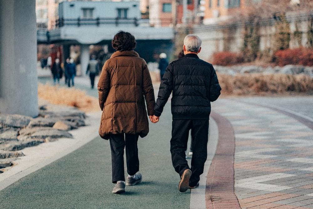 man in brown jacket and gray pants walking on sidewalk during daytime