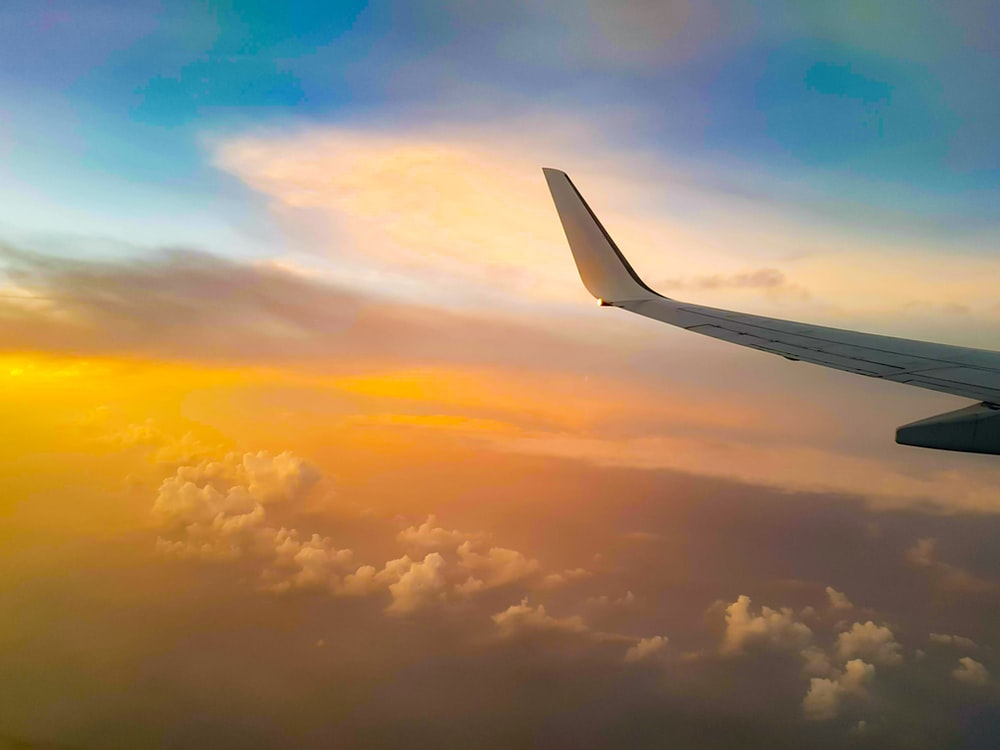 white airplane wing under white clouds during daytime