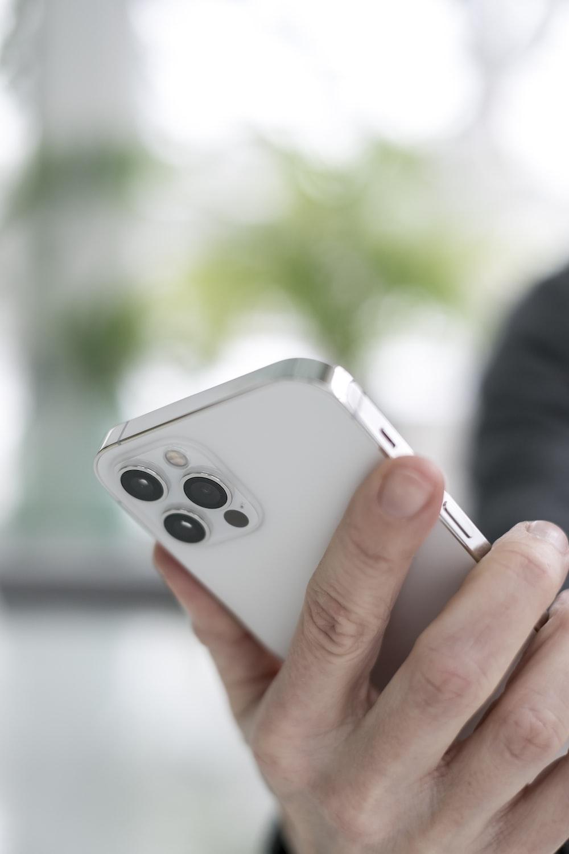person holding silver apple remote