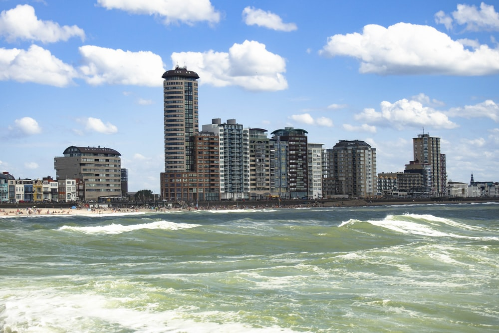 high rise buildings near sea under blue sky during daytime