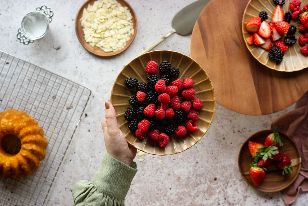 person holding bowl of strawberries