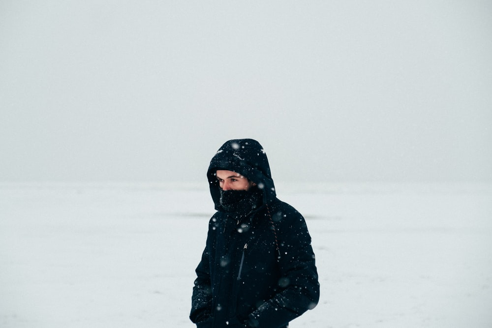 woman in black coat standing on snow covered ground