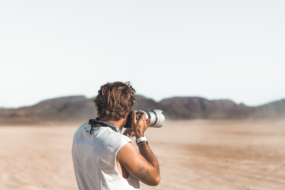 man in white t-shirt holding camera