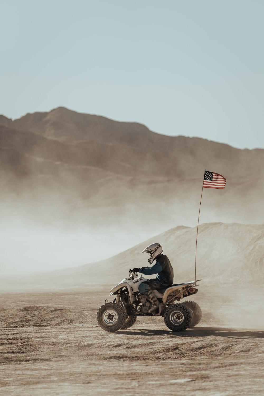 man riding atv on brown field during daytime