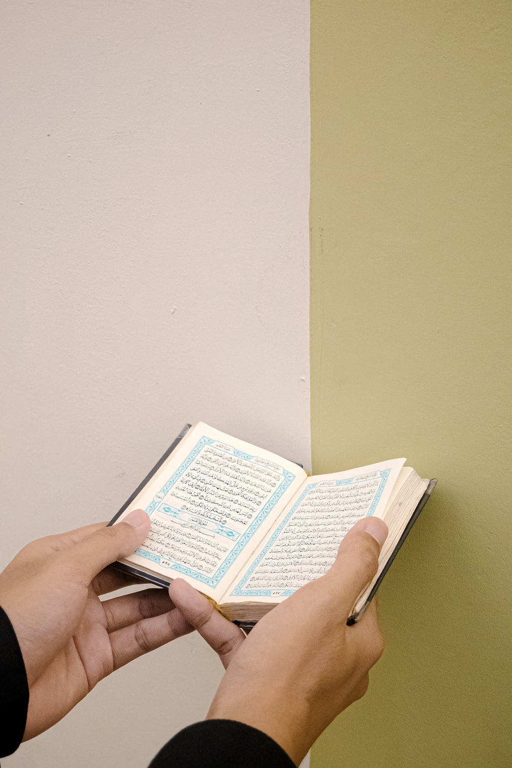 person holding white and blue book