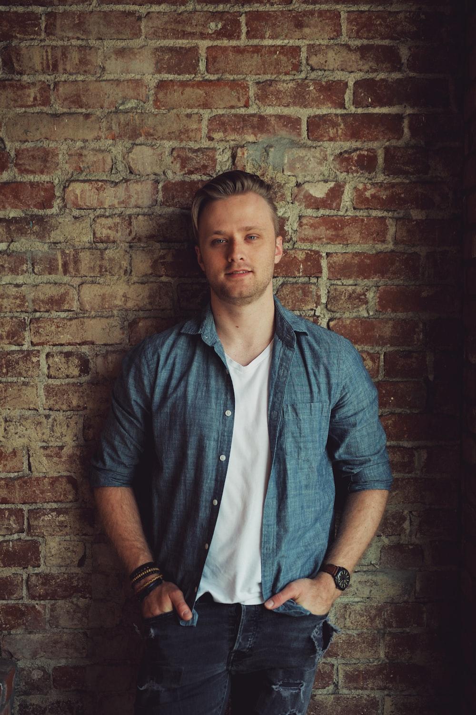 man in blue button up shirt standing beside brown brick wall