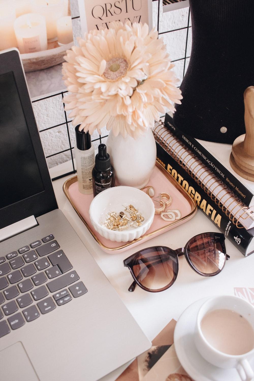 black framed sunglasses beside white flower