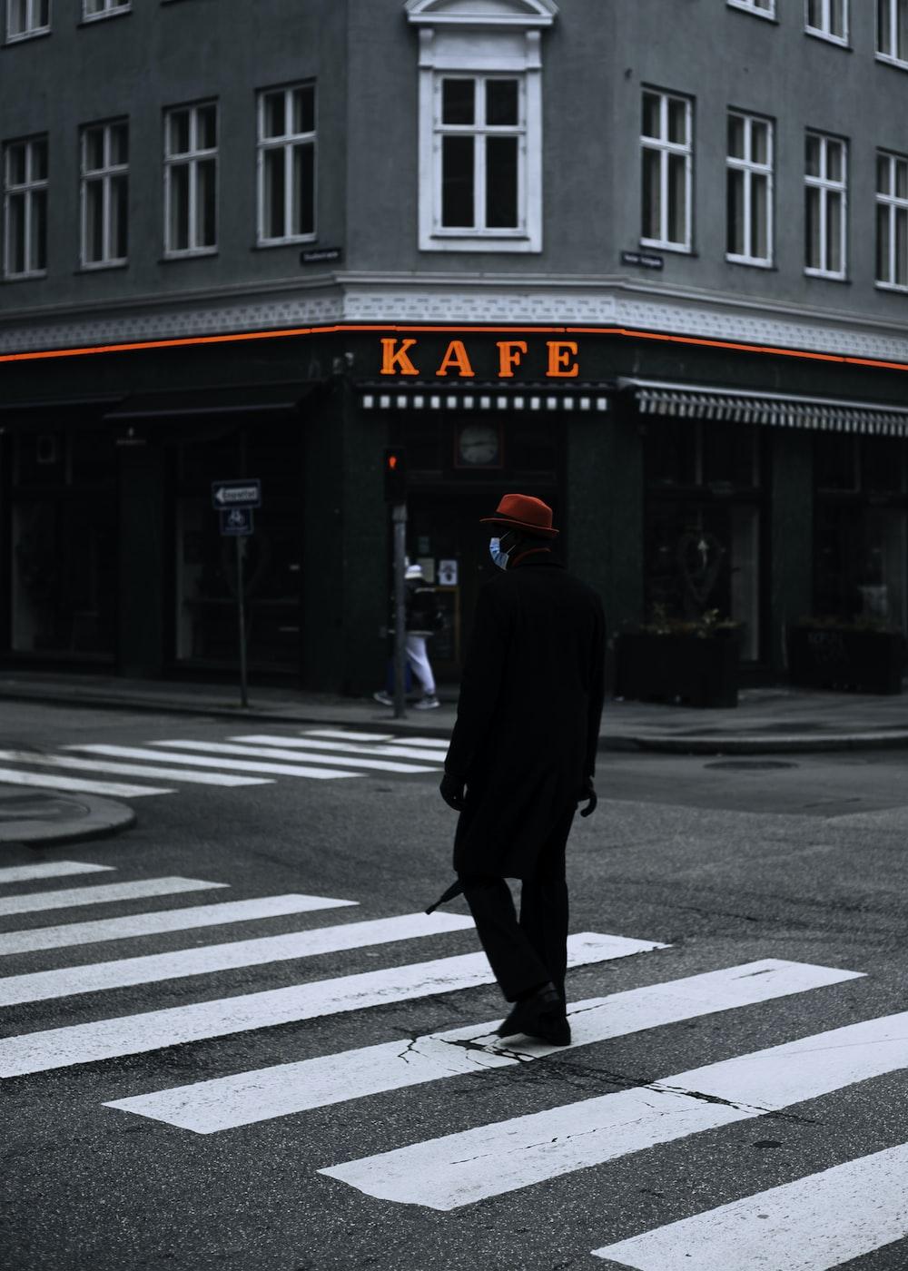 man in black coat walking on pedestrian lane during daytime