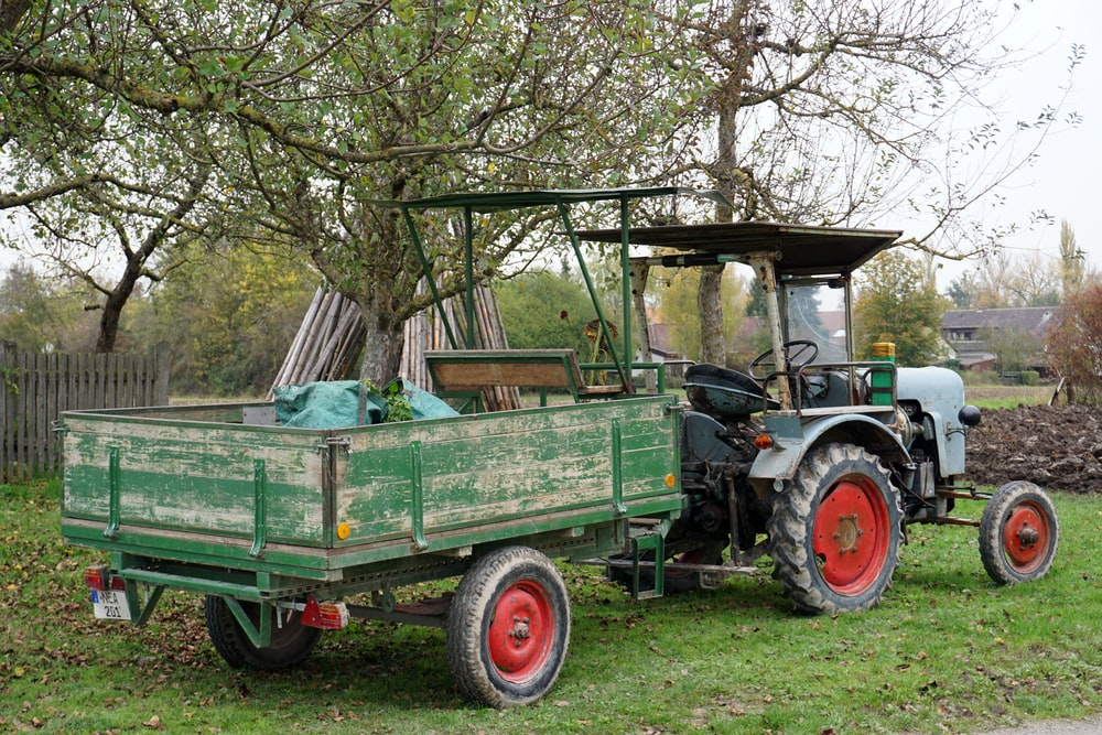 green and brown tractor on green grass field during daytime