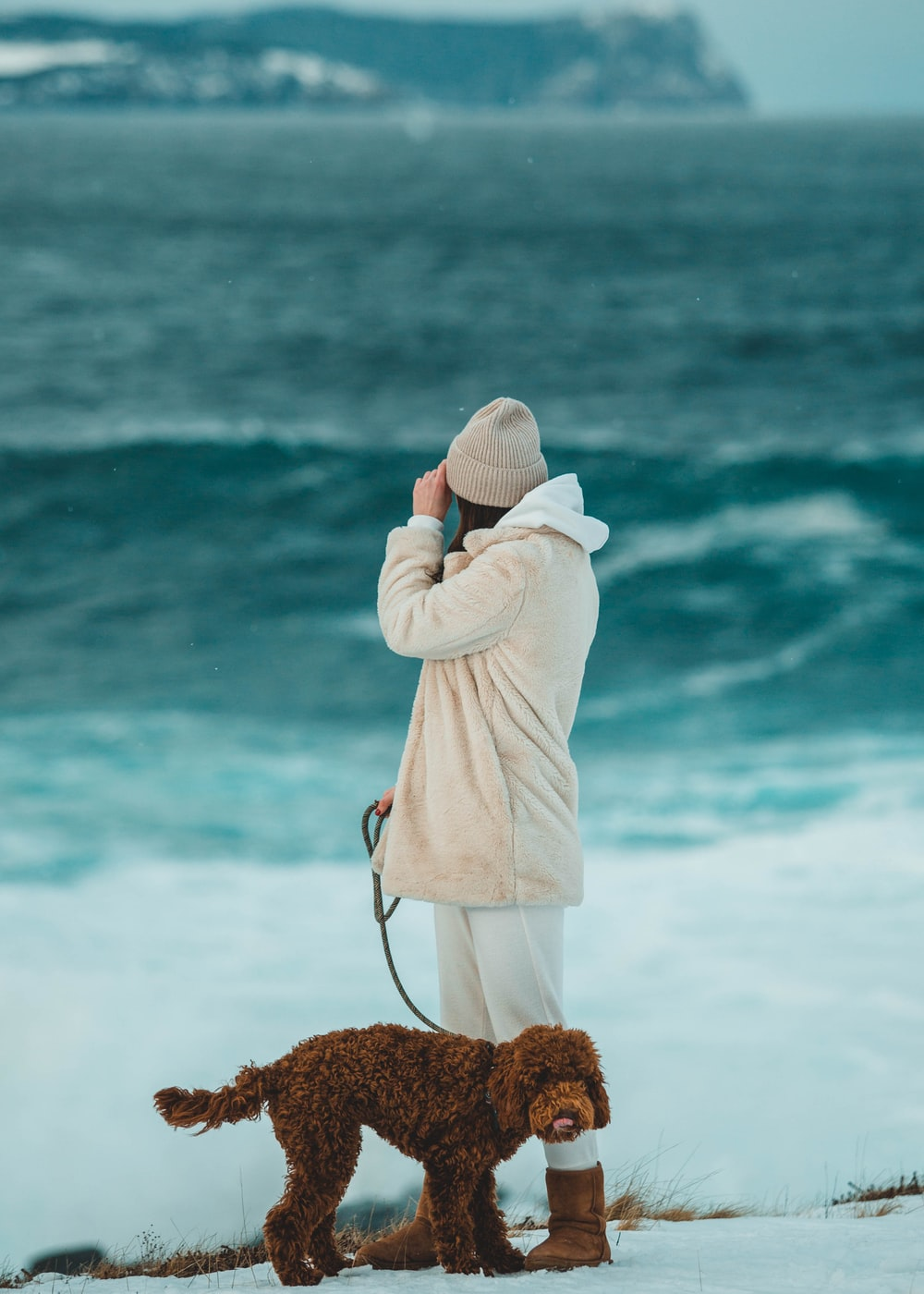 woman in white hoodie and white knit cap standing on seashore during daytime