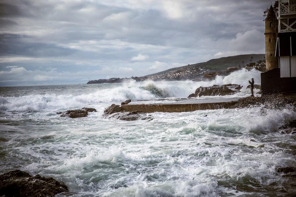 ocean waves crashing on brown rock formation under white clouds during daytime