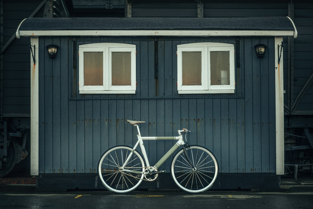 white and blue city bike parked beside gray wooden house