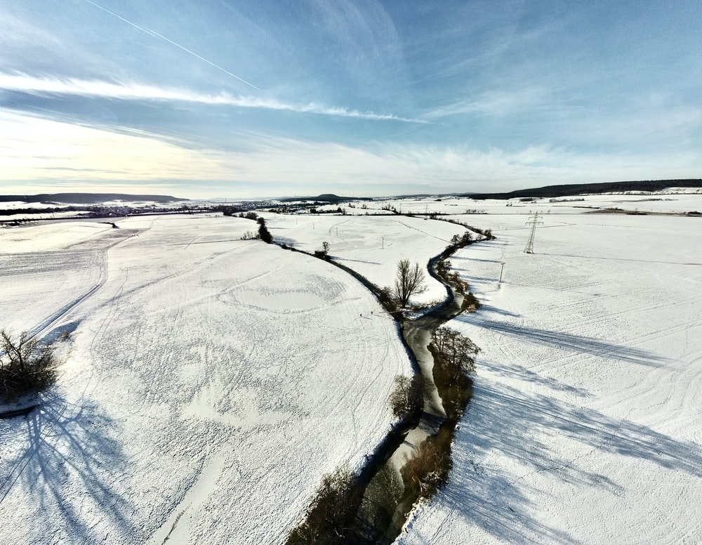 white snow covered field under blue sky during daytime