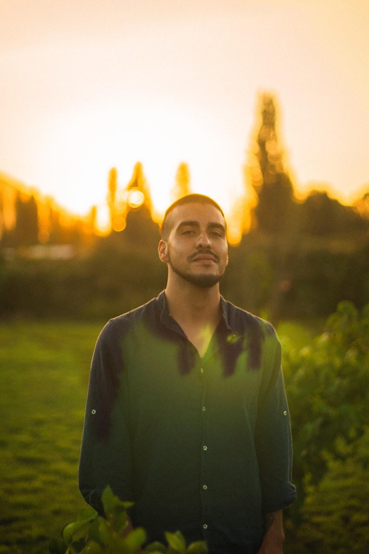 man in green dress shirt standing on green grass field during sunset