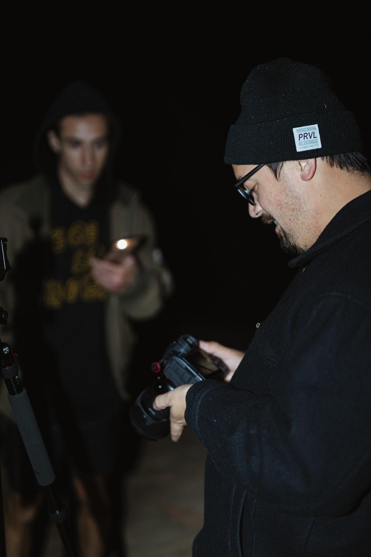 man in black jacket wearing black cap holding black dslr camera