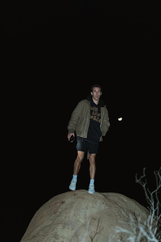 man in black jacket standing on brown rock