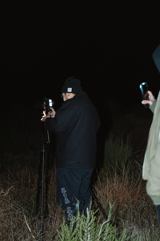 man in black hoodie holding black dslr camera