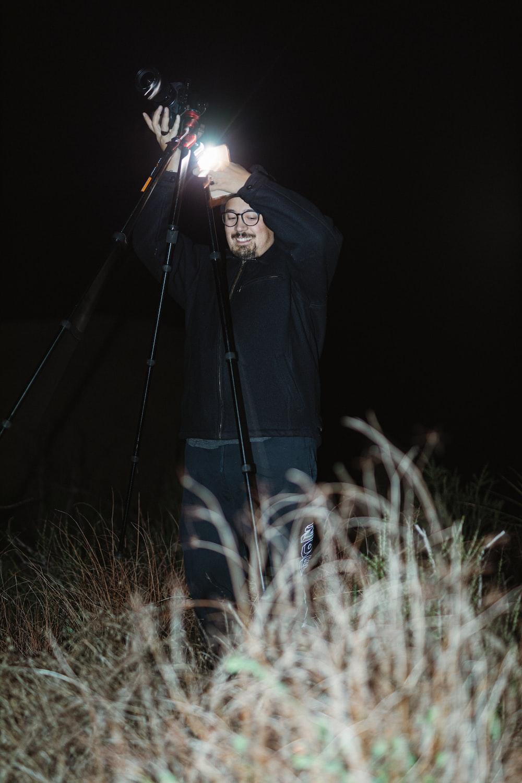 person in black jacket holding lighted sparkler
