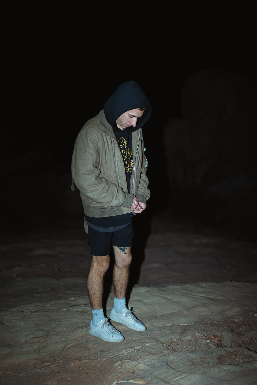 man in gray hoodie and black shorts standing on sand during nighttime