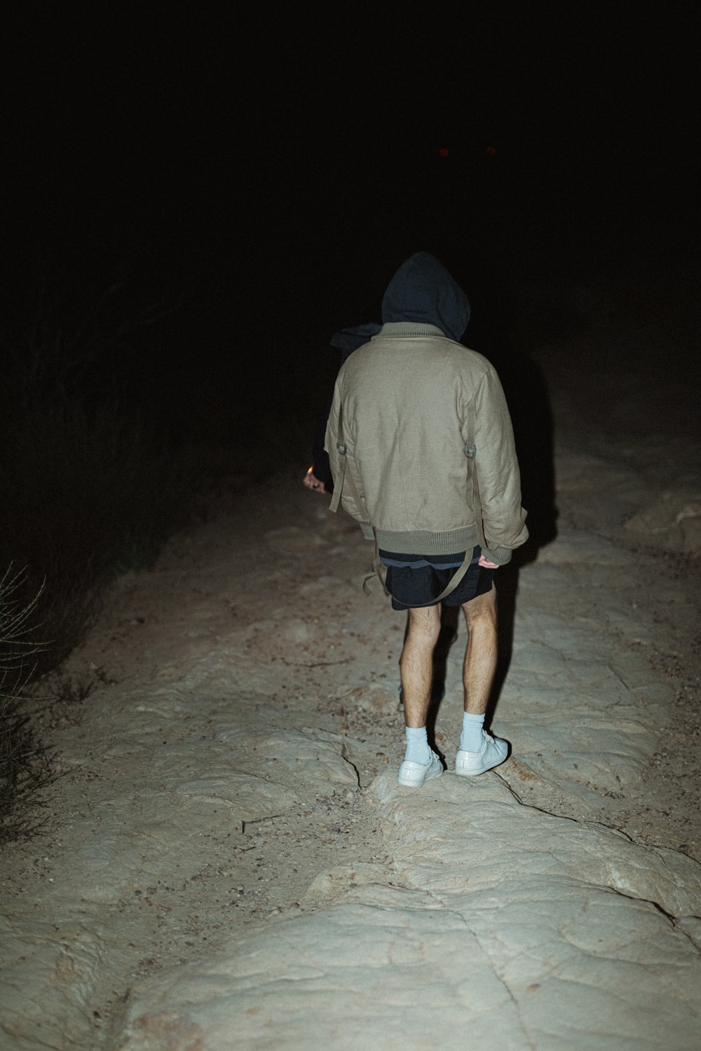 man in gray hoodie and blue shorts standing on gray sand during nighttime