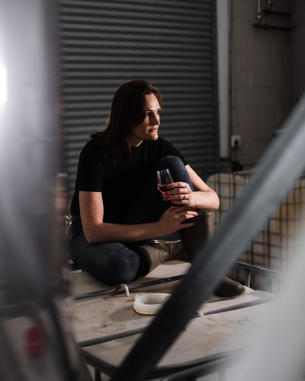 woman in black crew neck t-shirt and blue denim jeans sitting on white concrete floor