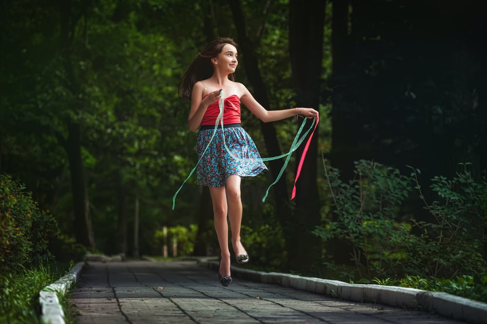 woman in red and white stripe dress standing on gray concrete pathway