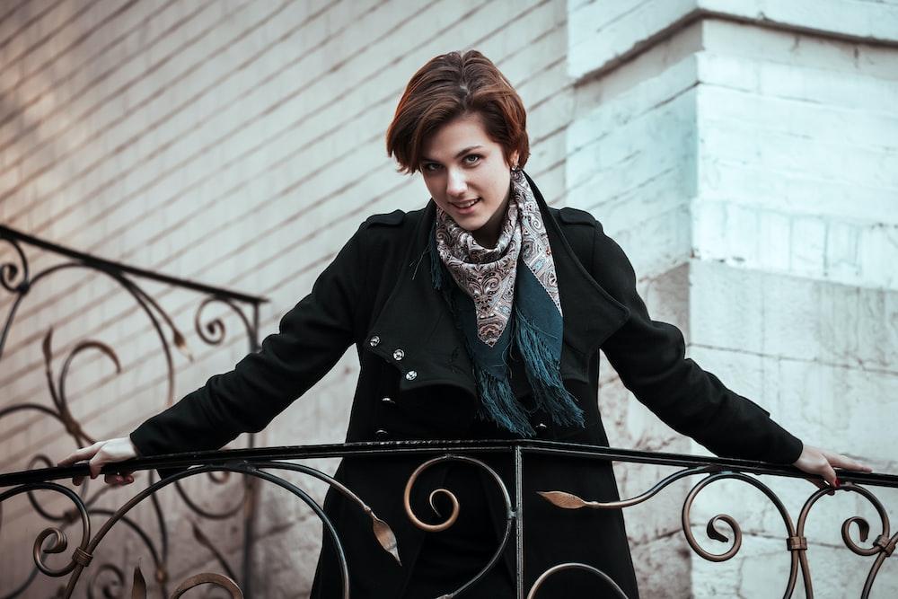 woman in black coat standing beside black metal fence during daytime