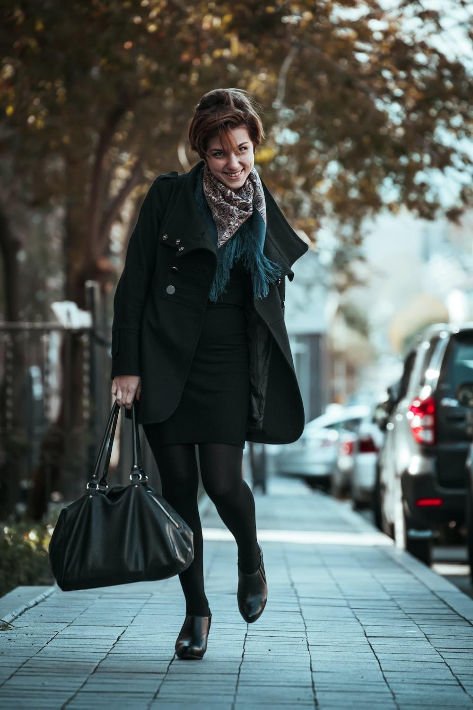 woman in black coat holding black leather handbag