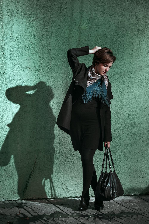 woman in black long sleeve dress standing on gray concrete floor