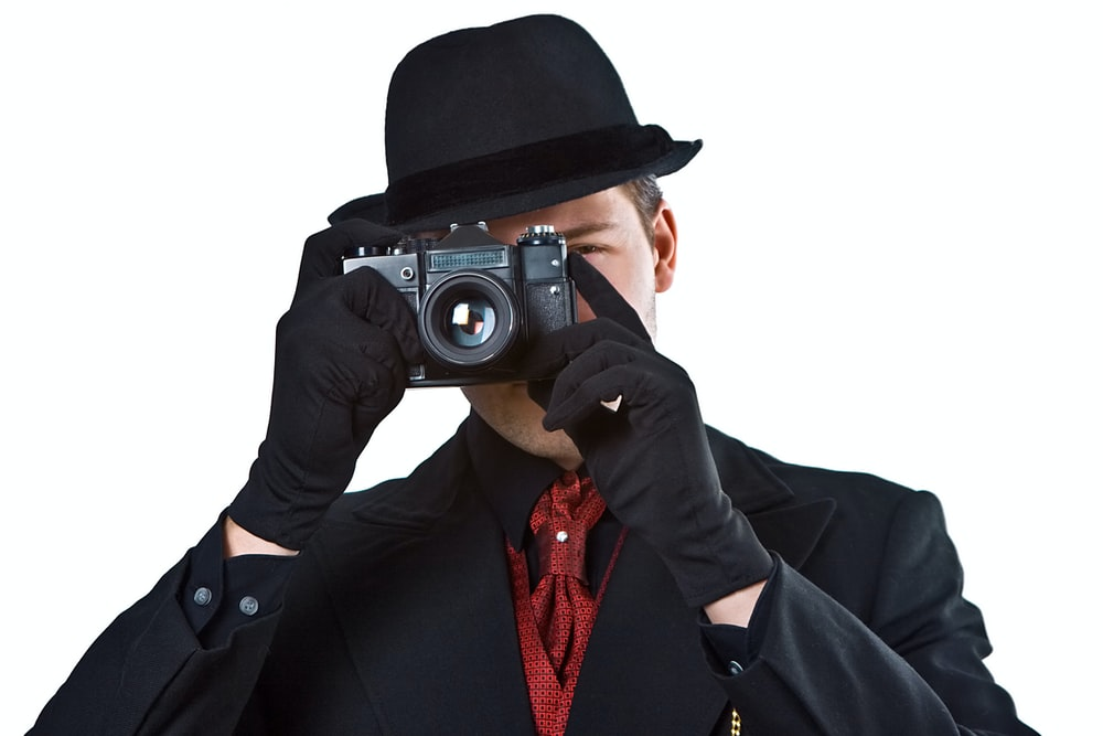 man in black blazer holding black camera