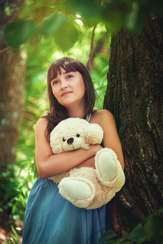 girl in blue sleeveless dress holding white bear plush toy