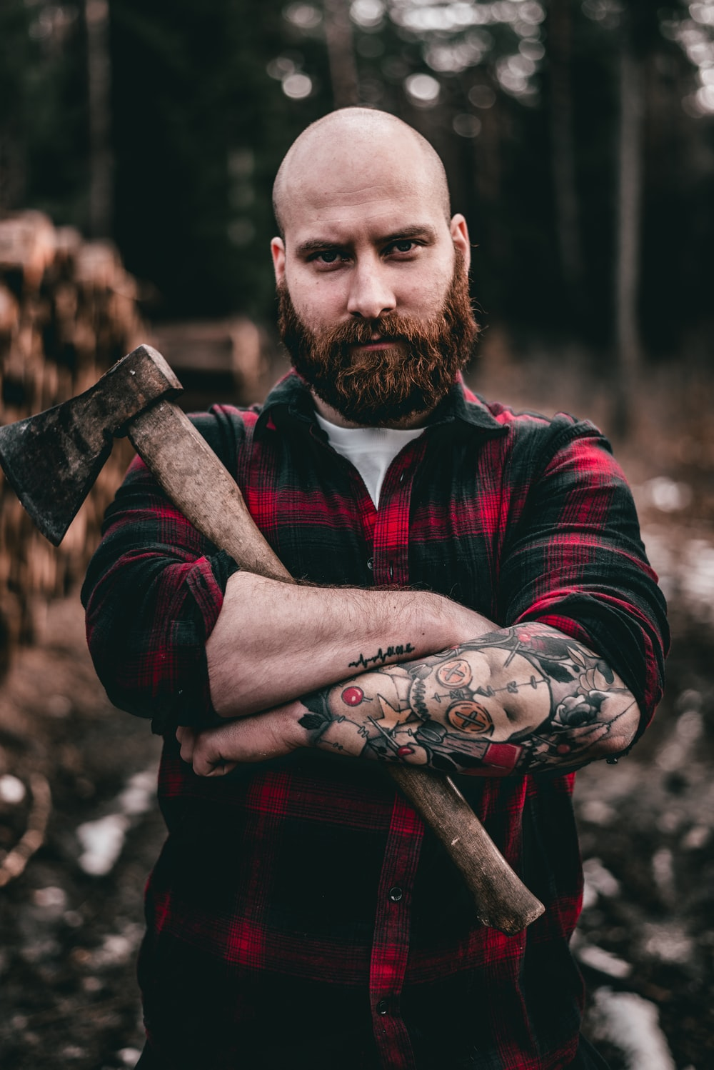 man in red and black plaid dress shirt holding brown wooden stick
