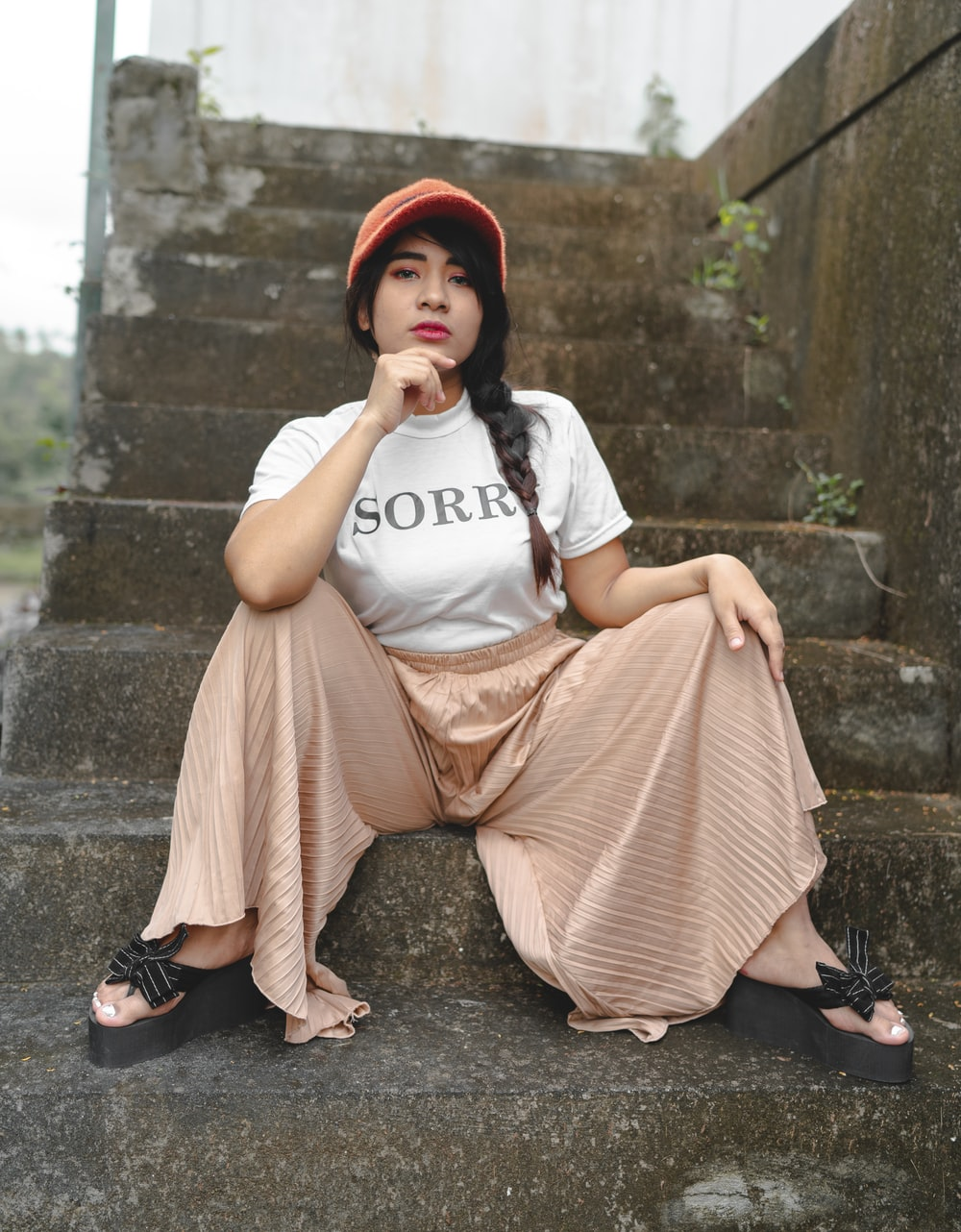 woman in white t-shirt and pink skirt sitting on concrete stairs