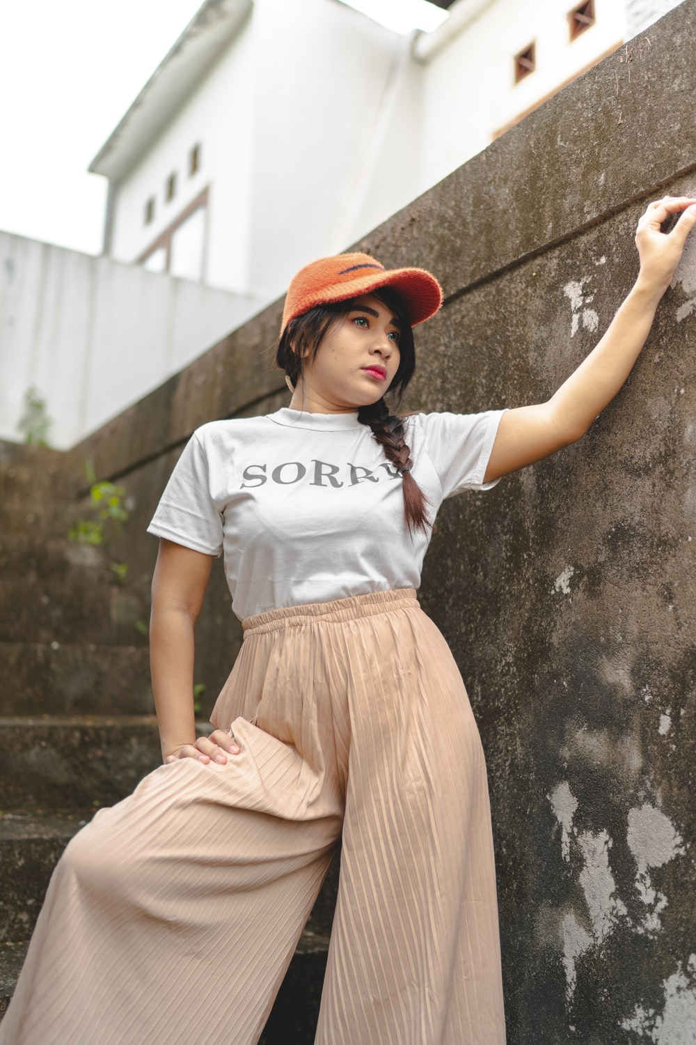 woman in white t-shirt and brown skirt leaning on wall