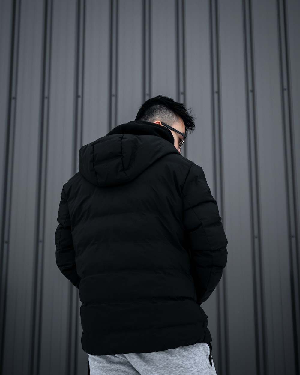 man in black hoodie standing in front of white wall