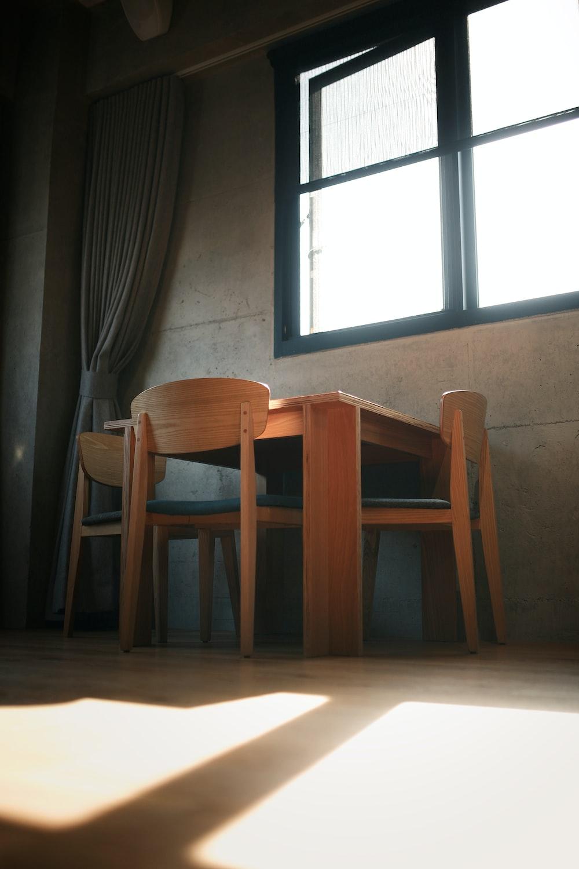 brown wooden chairs beside window