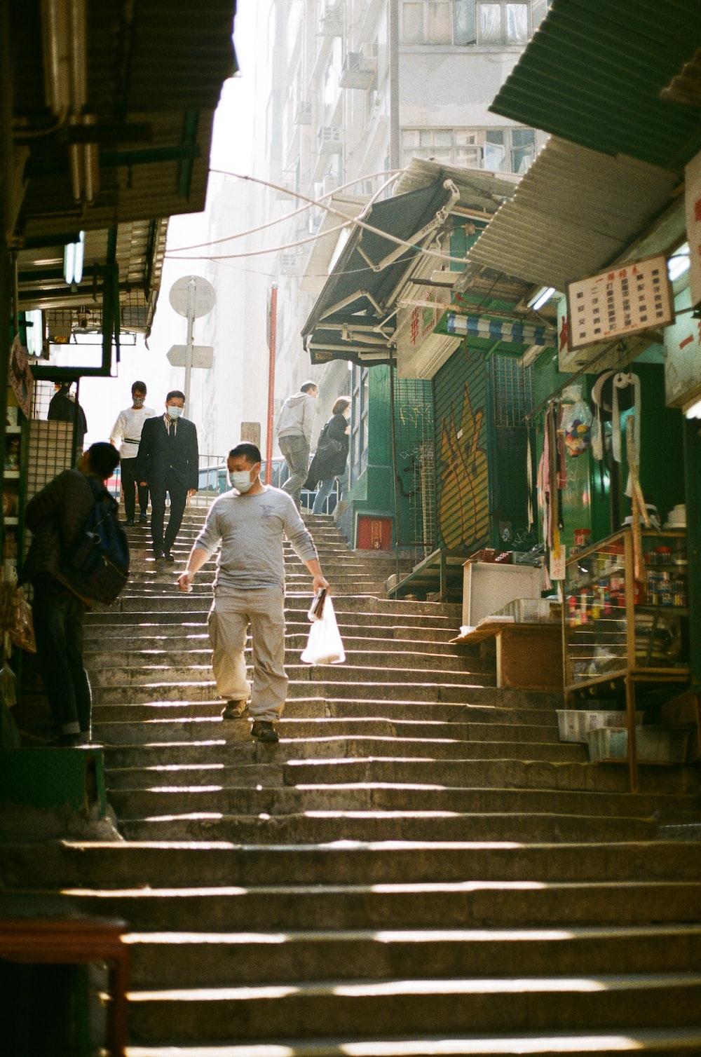 man in gray dress shirt walking on sidewalk during daytime