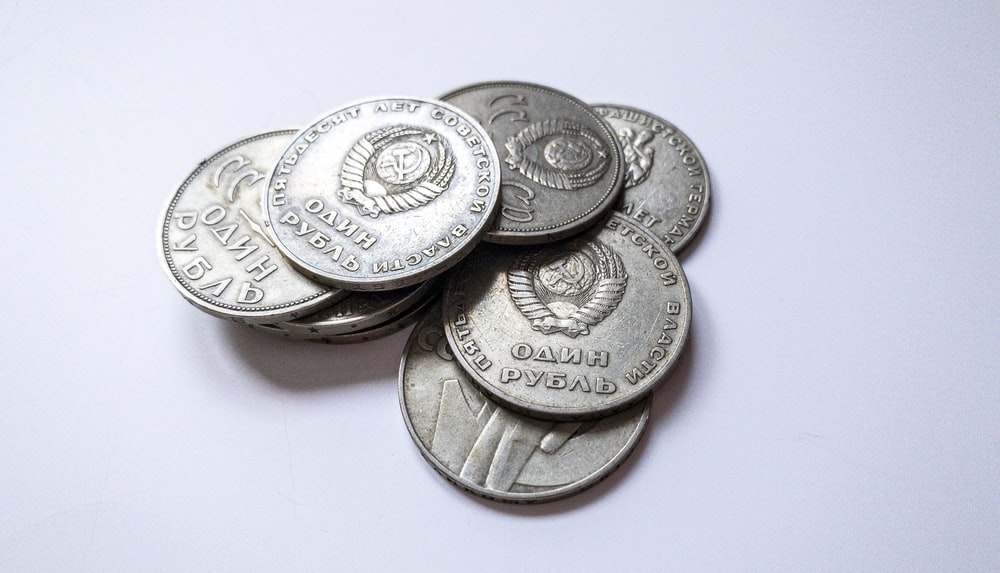 silver and gold coins on white surface