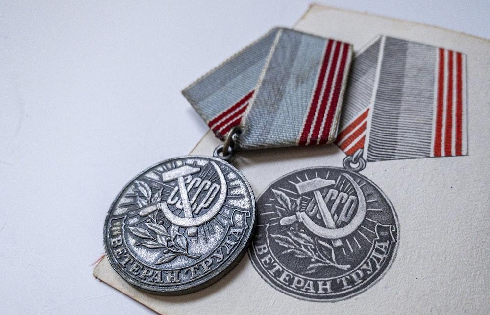silver round coin on white textile
