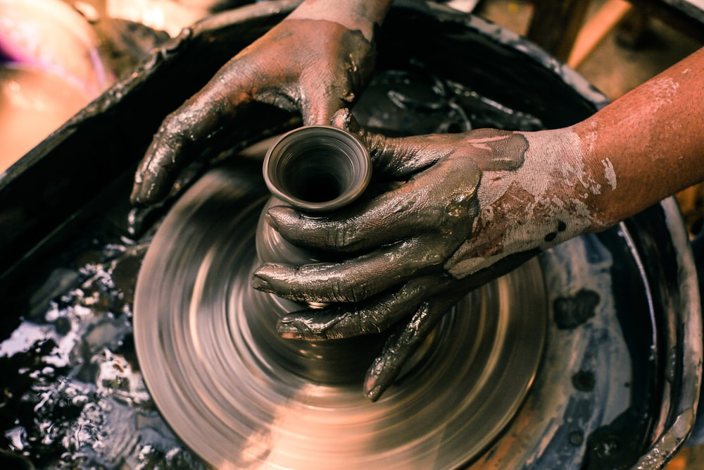 person making clay pot with water
