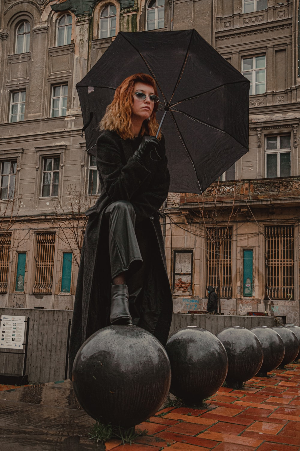 woman in black coat holding umbrella standing near brown concrete building during daytime