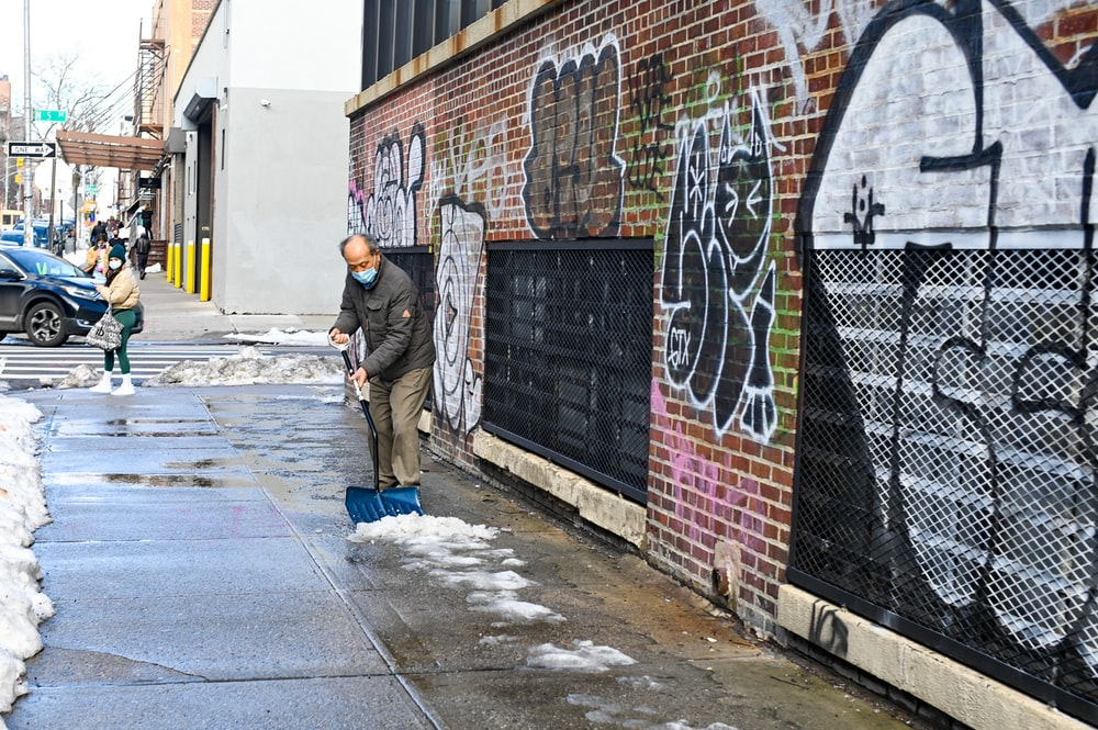 man in black jacket and blue denim jeans standing beside wall with graffiti during daytime