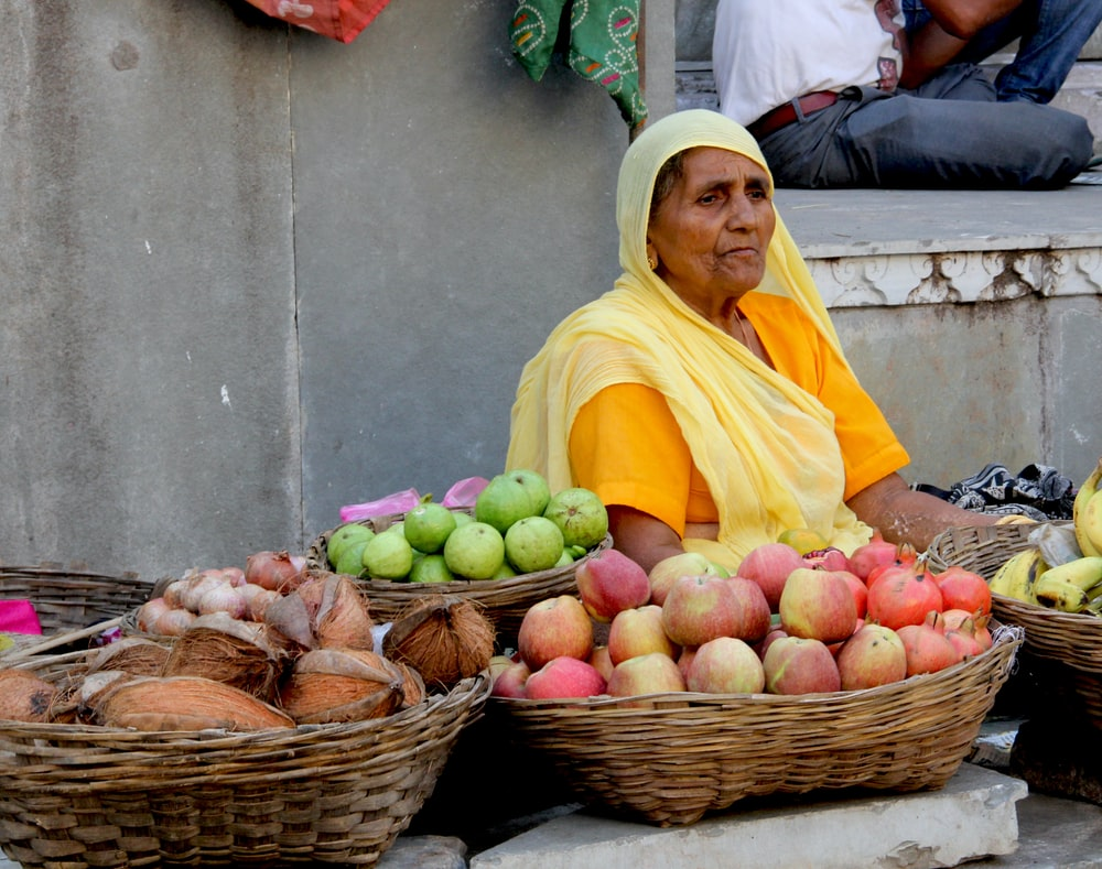 woman in yellow hijab and yellow dress holding red apples