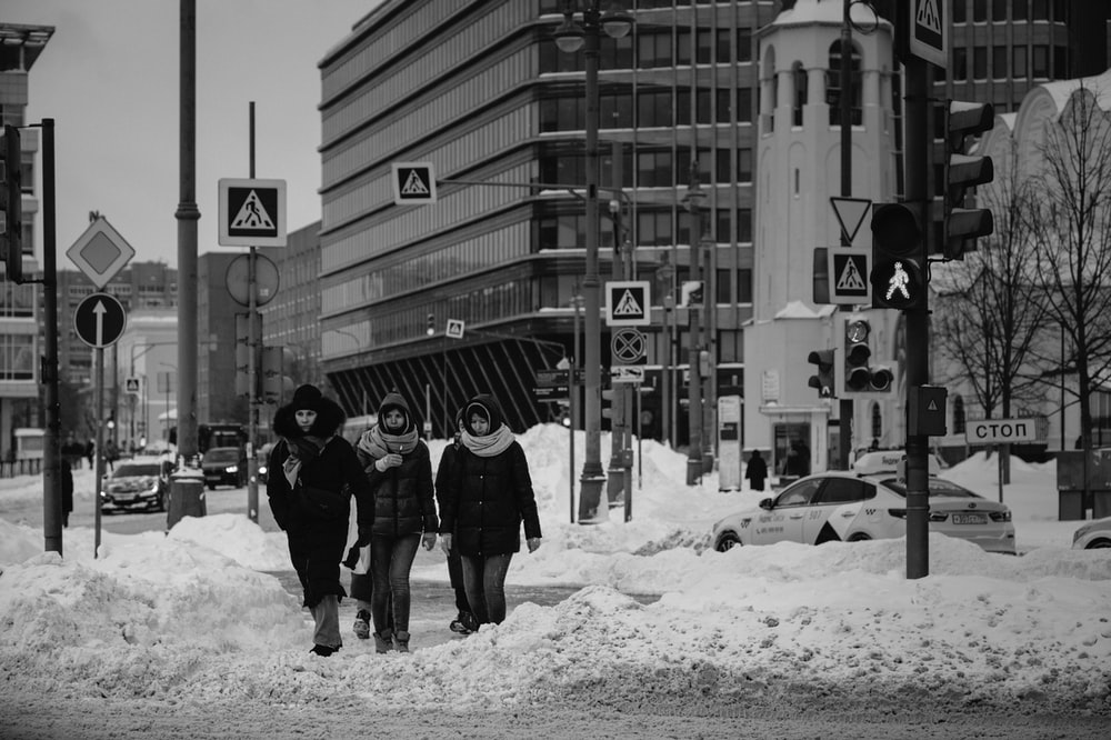 grayscale photo of 2 person walking on snow covered ground